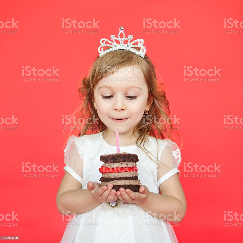 delighted little girl blowing the candles stock photo