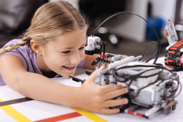 begeistert kleine schülerin, die erforschung neuer technologien in der schule - lernfortschrittskontrolle stock-fotos und bilder