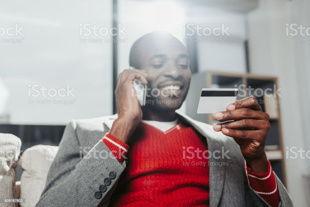 Delighted man chatting by cellphone and examining bankcard stock photo