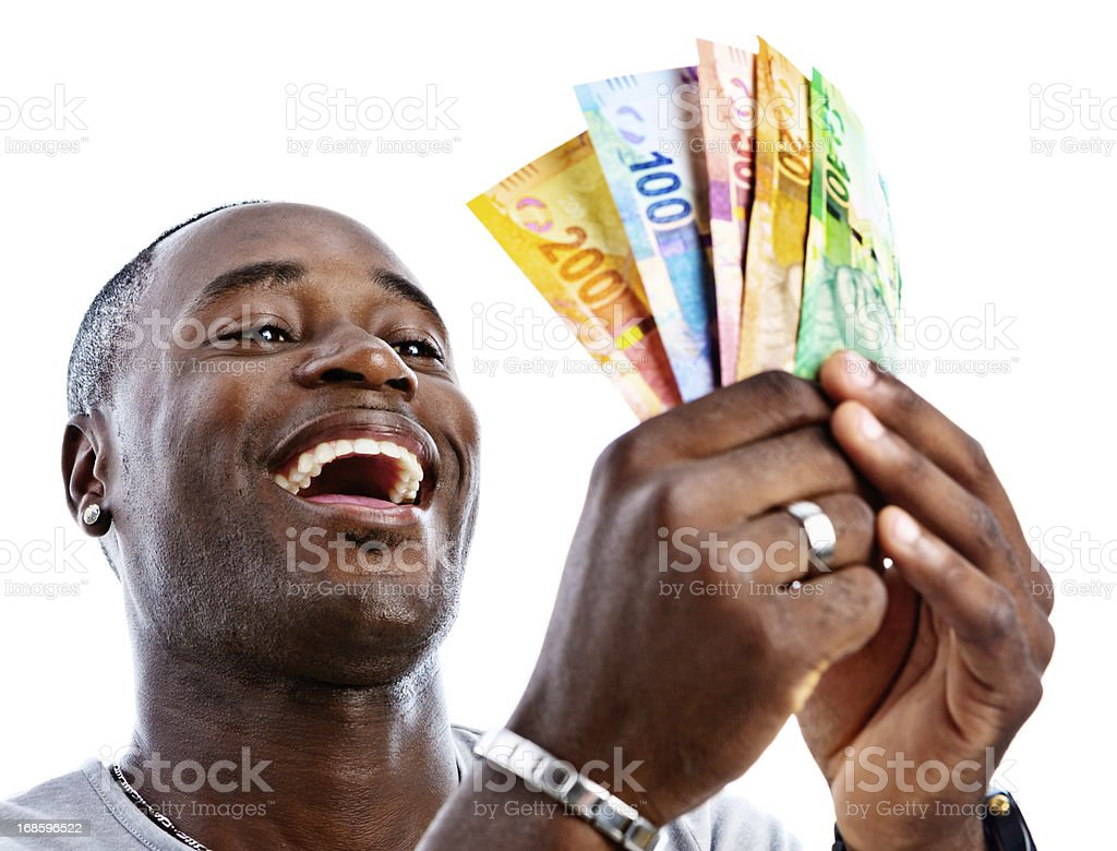 Delighted man holds sheaf of new South African banknotes stock photo
