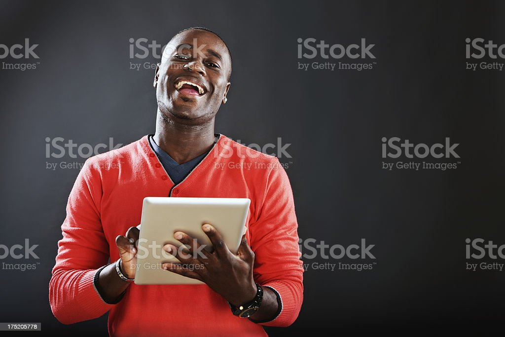 Delighted man looks up laughing from digital tablet stock photo
