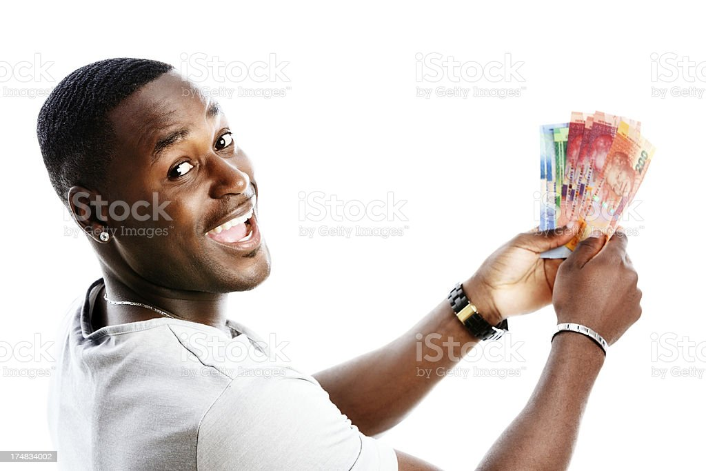 Delighted man with South African banknotes smiles over his shoulder stock photo