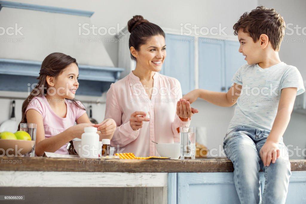 Madre encantada desayunando con sus hijos - foto de stock