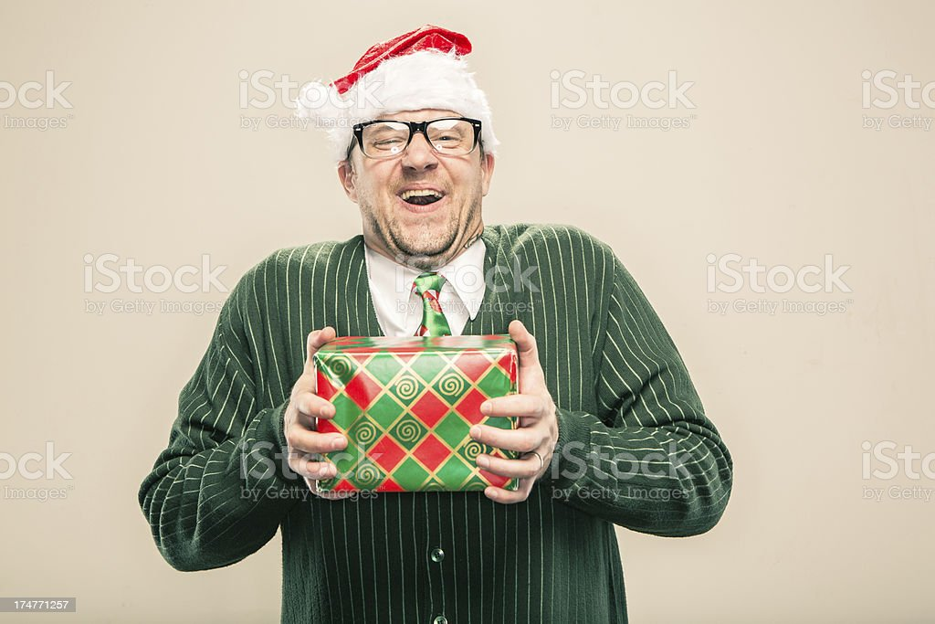 delighted Nerdy Christmas Man holding wrapped holiday gift stock photo