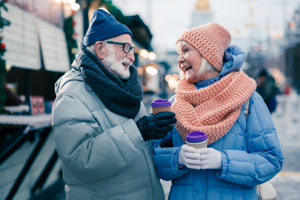 Delighted pensioners laughing while meeting at the winter street stock photo