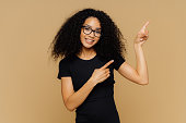 Delighted pleased dark skinned female points at upper right corner, shows place for your advertising content, wears glasses and black t shirt, isolated over brown studio wall. Promotion concept