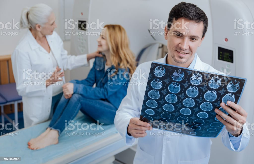 Delighted positive doctor holding CT scan results royalty-free stock photo
