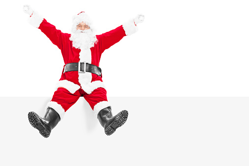 istock Delighted Santa Claus sitting on a blank panel 517678967