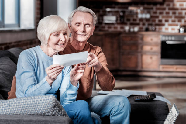 Delighted senior people being happy together Good for you. Smiling male person embracing his wife while pointing at counting social security stock pictures, royalty-free photos & images