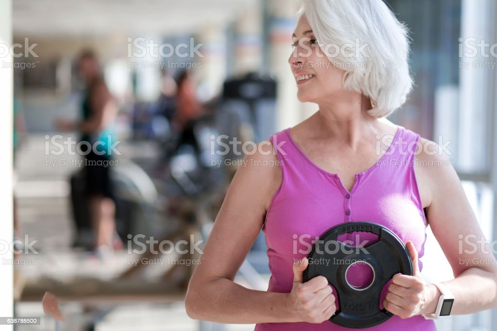 Delighted smiling woman exercising with sport equipment. stock photo