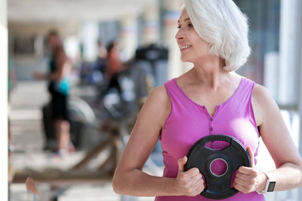 Delighted smiling woman exercising with sport equipment. - foto stock