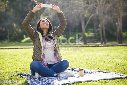 Delighted student girl taking selfie on phone outdoors. Young woman in casual jacket resting on plaid in park, and photographing sky on her smartphone. Picturing concept