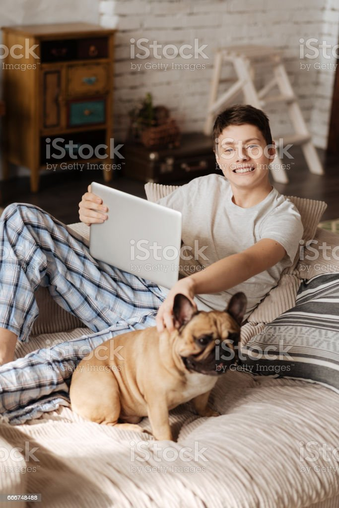 Delighted teenager posing on camera with his pet foto stock royalty-free