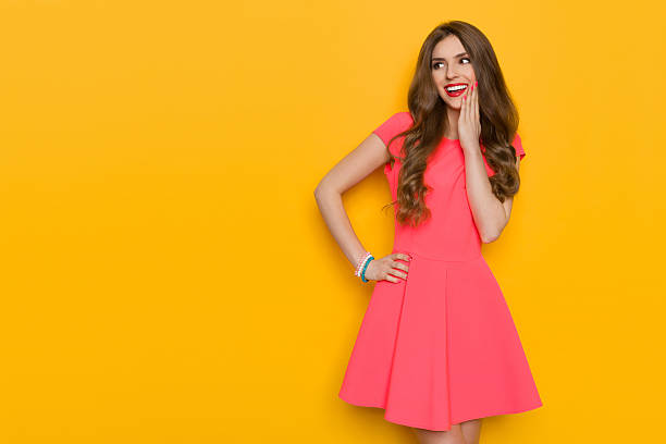 delighted woman in pink dress looking away - mini dress stock photos and pictures