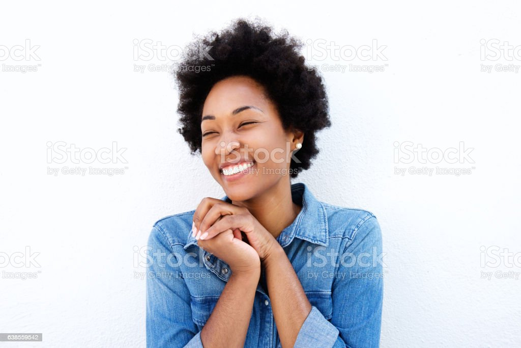 Delighted woman smiling by white wall stock photo