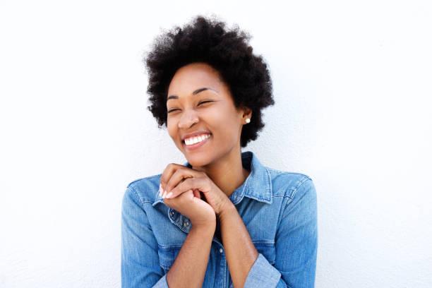 delighted woman smiling by white wall - menschen lachen stock-fotos und bilder