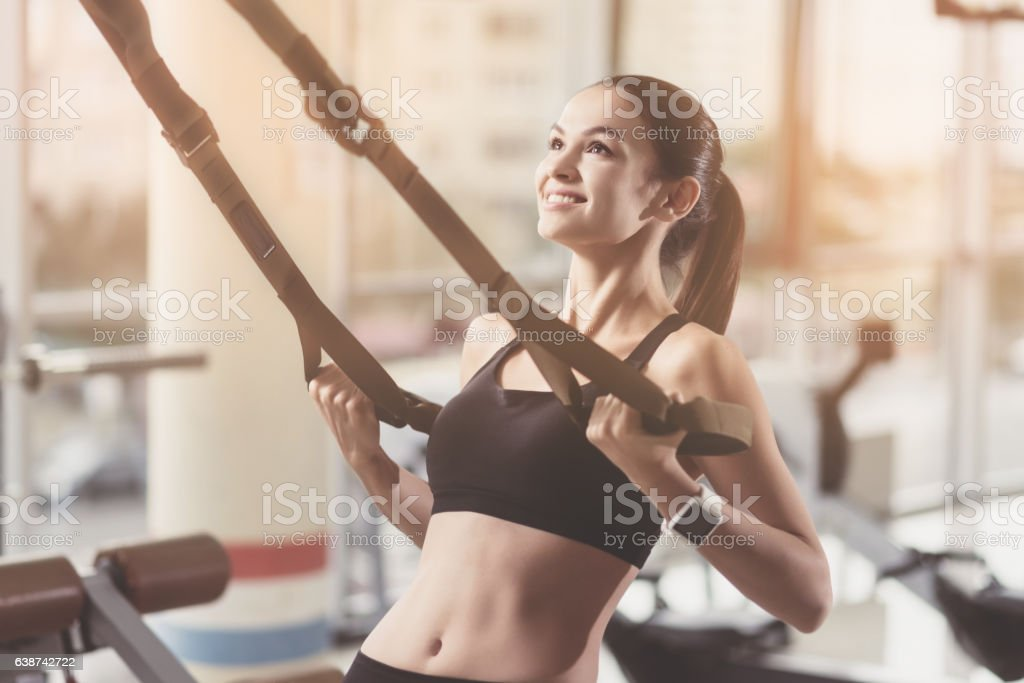 Delighted woman training hard in a gym stock photo