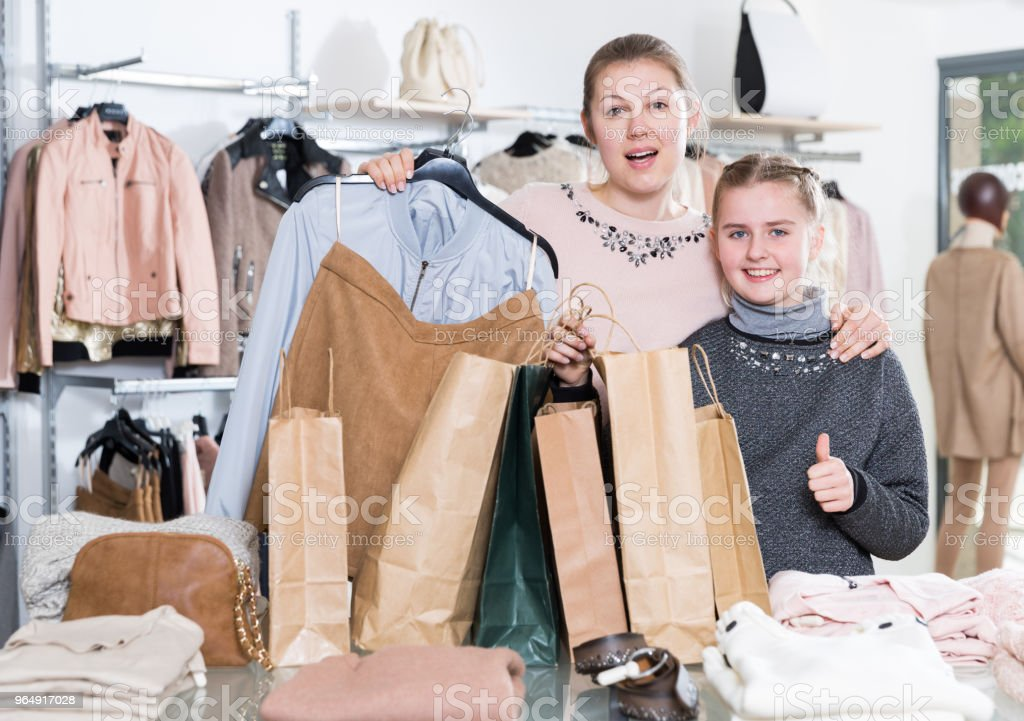 Delighted woman with daughter in clothing store royalty-free stock photo