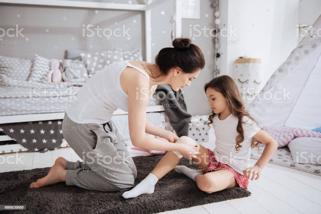 Delighted young mother bandaging her kid at home stock photo