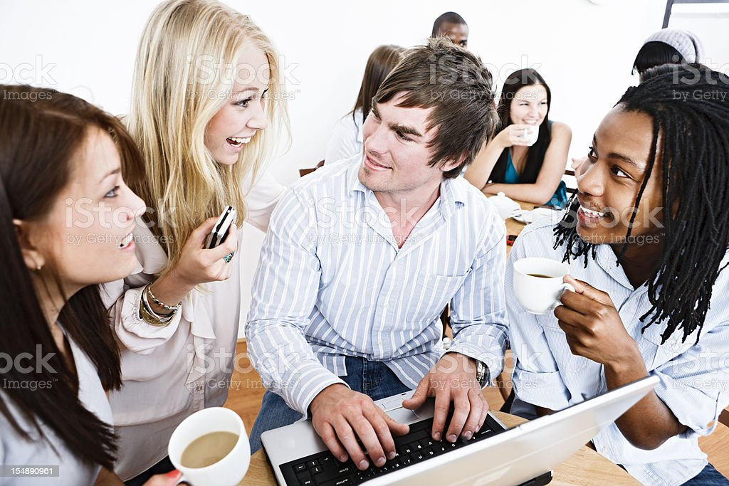 Delighted young people smile round laptop in coffee shop royalty-free stock photo