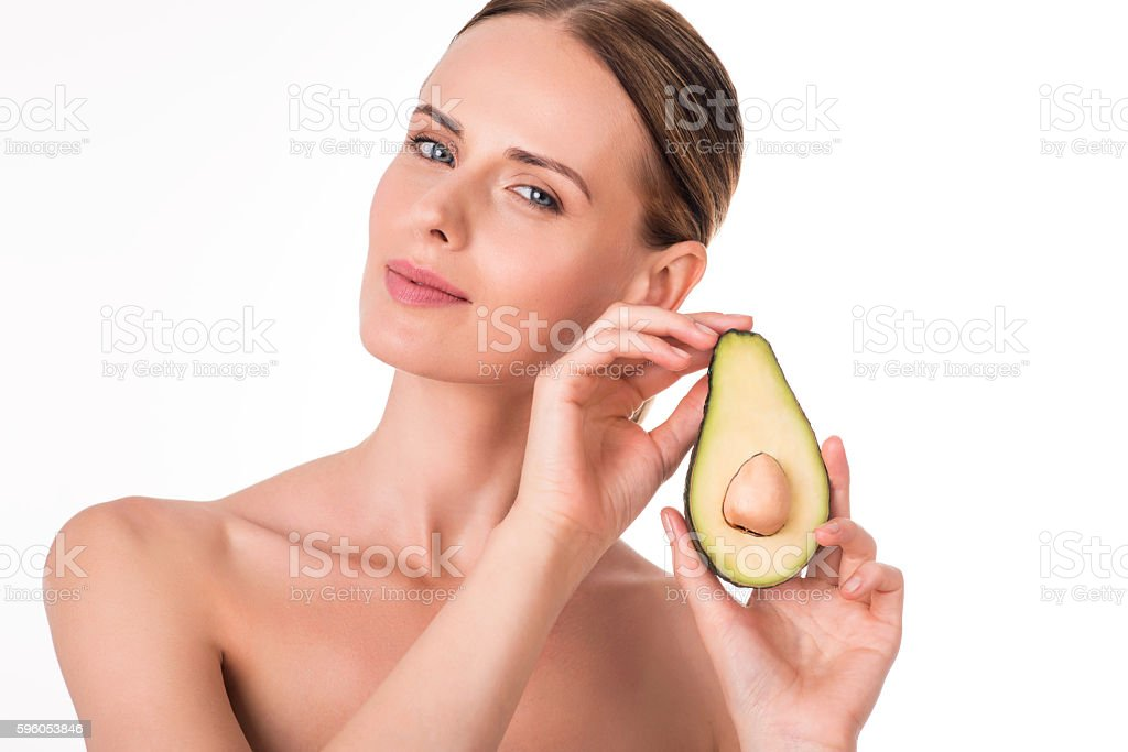 Delighted young woman holding part of avocado royalty-free stock photo