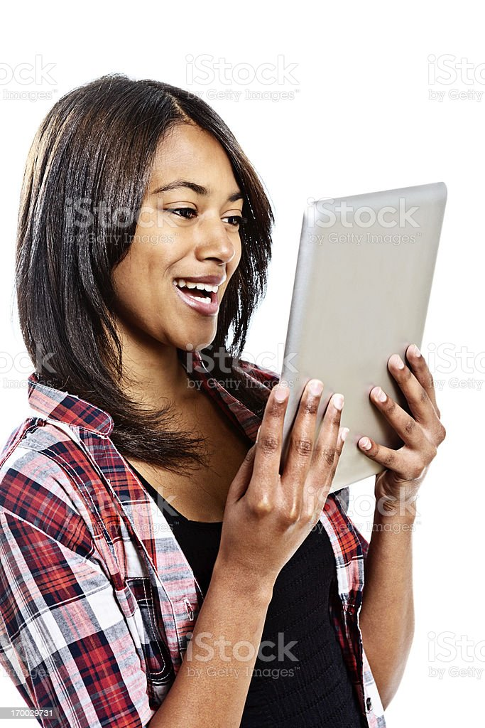 Delighted young woman looks down laughing at digital tablet royalty-free stock photo
