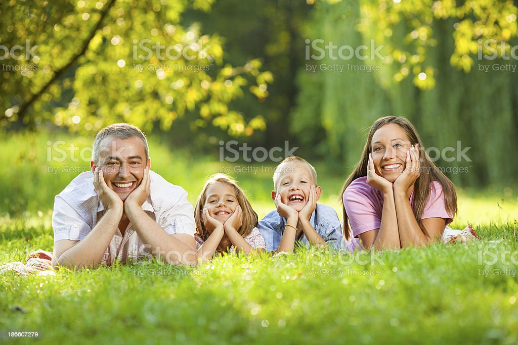 Delightful family smiling at camera in the park. royalty-free stock photo