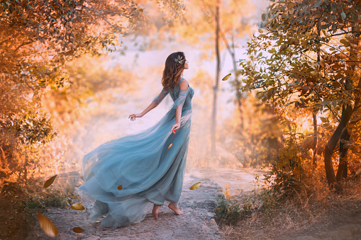istock delightful light girl in sky blue turquoise dress with long flying train, princess of wind and daughter of storm, lady with dark hair throws fallen leaves to ground, autumn story in art processing 1163568715