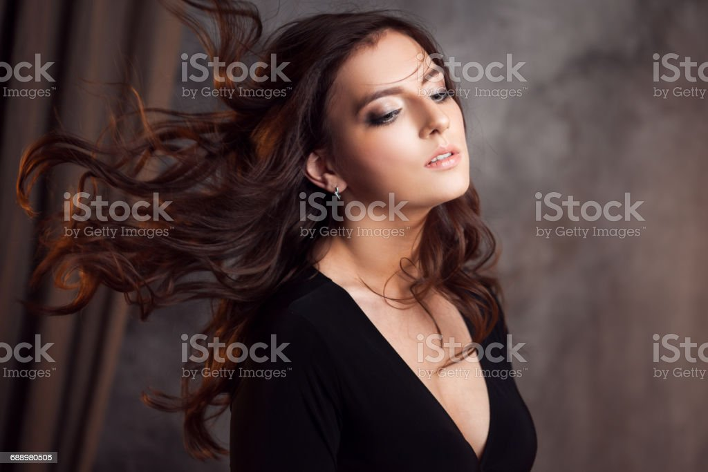 Delightful portrait of a woman brunettes, hair flying on the wind, sloppy styling stock photo