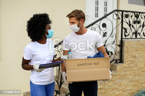 Group of people delivering donations to a house door. Two people, 25-35 years old, Caucasian man and an African female.