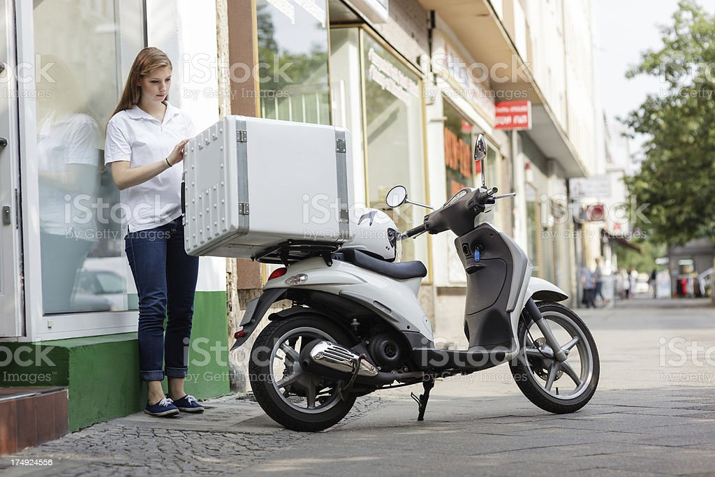 Young fast food delivery person getting to leave for a delivery, she...