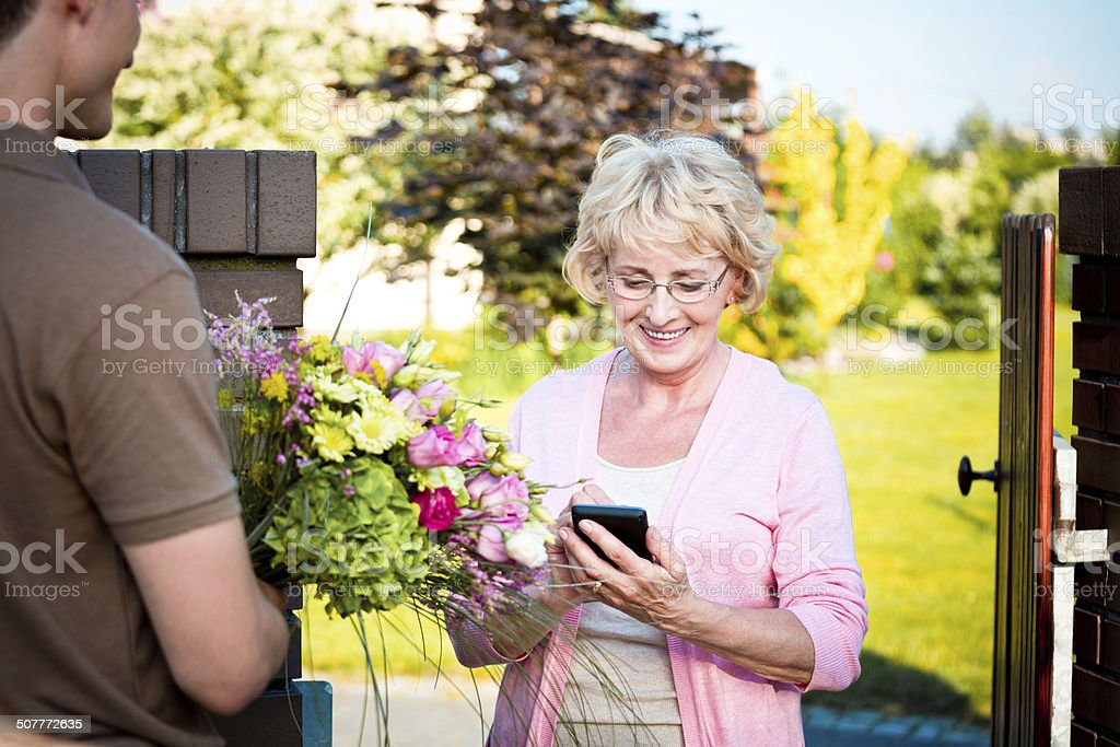 Delivering flowers Delivery man delivering a bouquet for senior lady. Woman signing up on palmtop. Outdoor shot. 60-64 Years Stock Photo