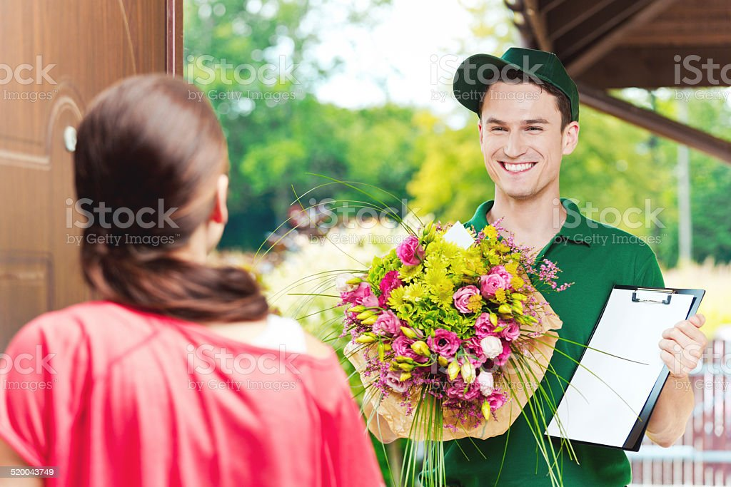 Delivering flowers Delivery man delivering a bouquet for young woman, standing in th entrance door and holding flowers and clip board. Adult Stock Photo