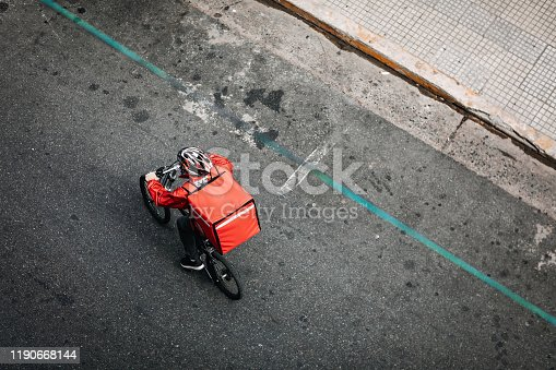 A young man working for a food delivery service in a sustainable way, riding bike