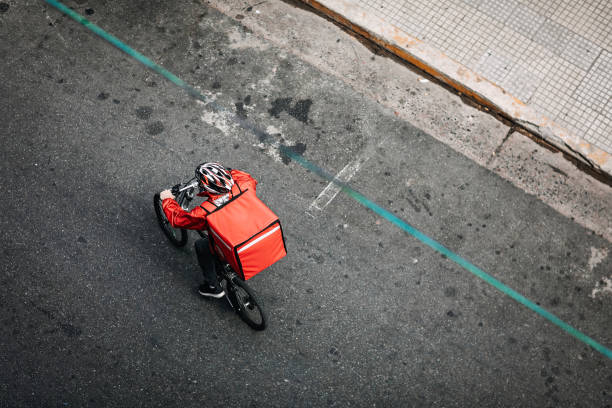 delivering food on bicycle in city - food delivery imagens e fotografias de stock