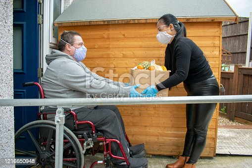 Helper Delivering Food to a Disabled Man in Quarantine During Covid19 Coronavirus Pandemic
