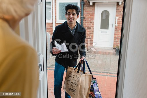 Teenage boy is delivering a bag of shopping to an elderly woman at home.