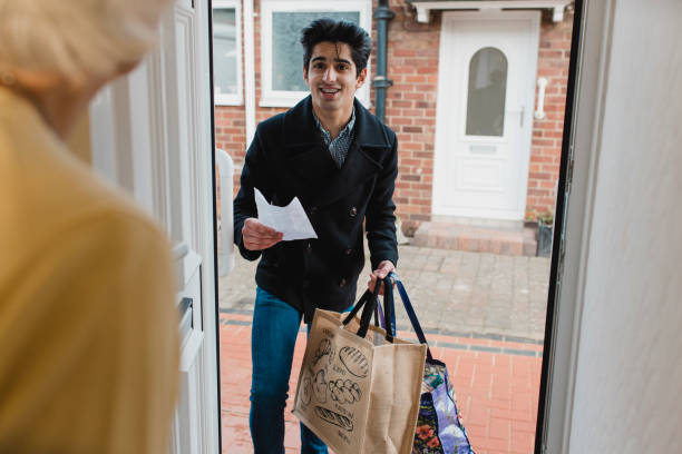 delivering groceries to an elderly woman - grocery home foto e immagini stock