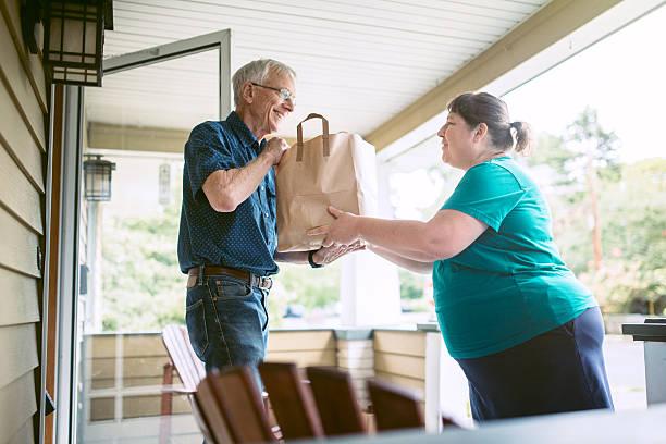 delivering groceries to senior man - einen gefallen tun stock-fotos und bilder
