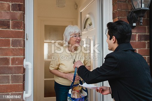 Teenage boy is delivering groceries to his grandmother.