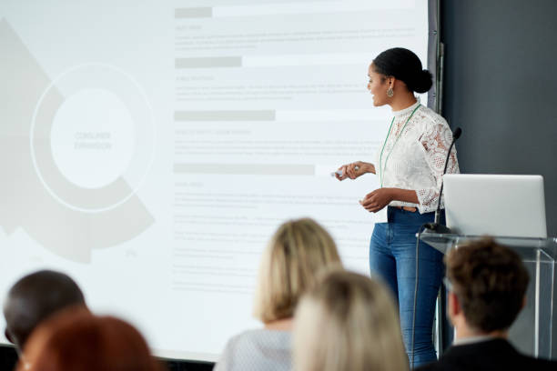 Delivering informative presentations is what she does best Shot of a young businesswoman delivering a presentation at a conference presenter stock pictures, royalty-free photos & images