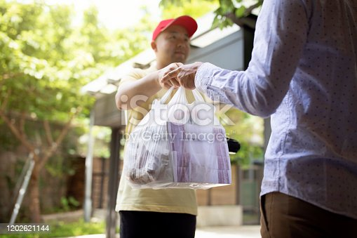 Asian man delivering take away food to customer at his home