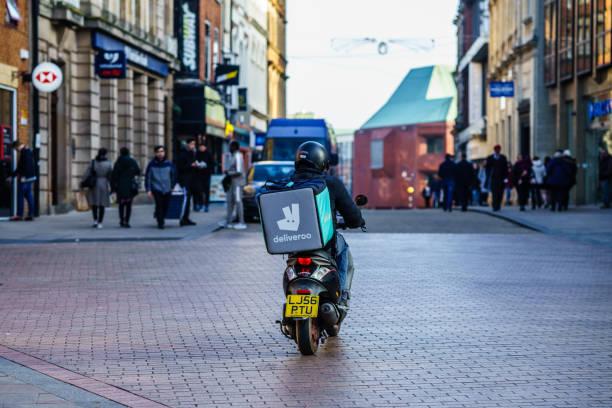 deliveroo, lebensmittel-lieferservice motorrad fahrer - kinder die schnell arbeiten stock-fotos und bilder