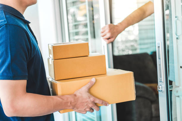 Delivery Asian man service with boxes in hands standing in front of Customer's house doors stock photo