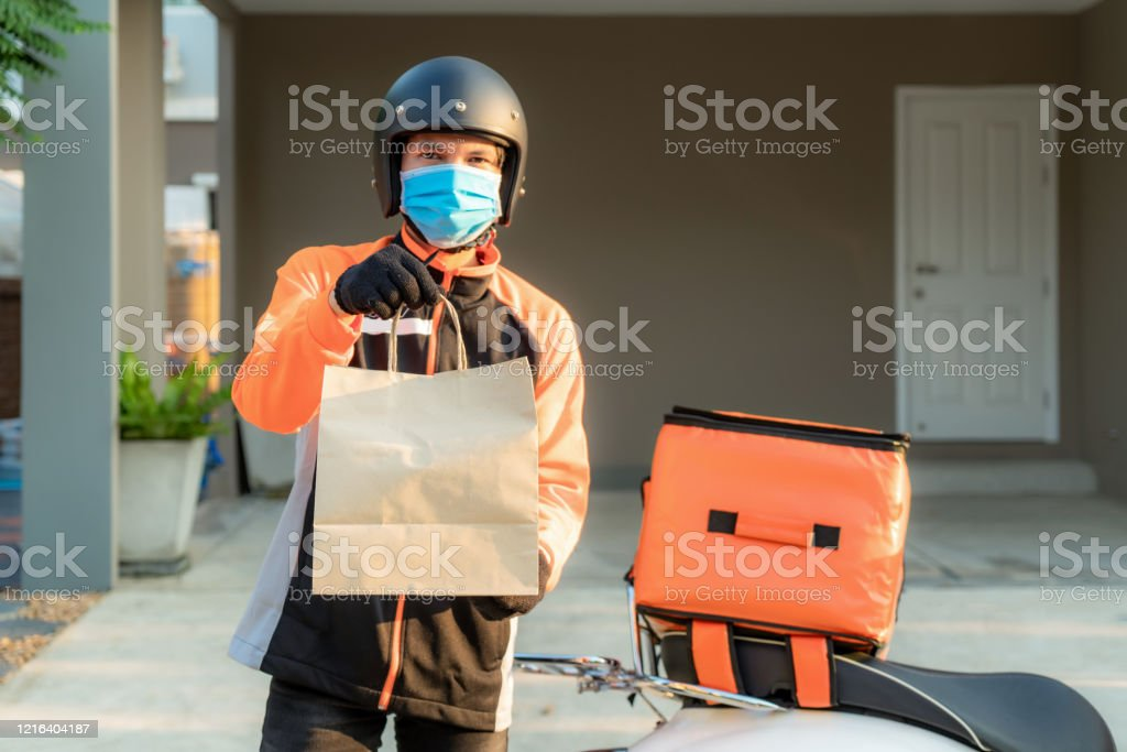 Delivery Asian man wear protective mask in orange uniform and ready to send delivering Food bag in front of customer house with case box on scooter, express food delivery and shopping online concept. - Zbiór zdjęć royalty-free (Aplikacja mobilna)