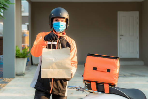delivery asian man wear protective mask in orange uniform and ready to send delivering food bag in front of customer house with case box on scooter, express food delivery and shopping online concept. - delivery стоковые фото и изображения