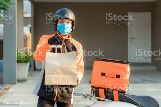 Delivery Asian Man Wear Protective Mask In Orange Uniform And Ready To Send Delivering Food Bag In Front Of Customer House With Case Box On Scooter Express Food Delivery And Shopping Online Concept - zdjęcia stockowe i więcej obrazów Aplikacja mobilna