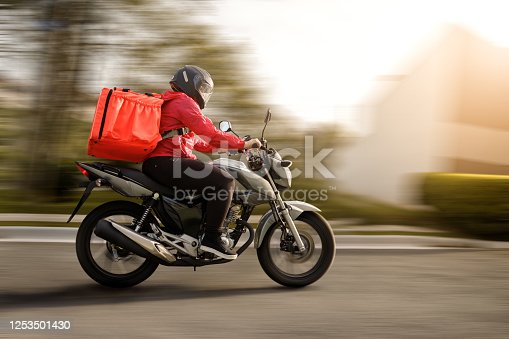 Delivery biker arriving at destination - motogirl