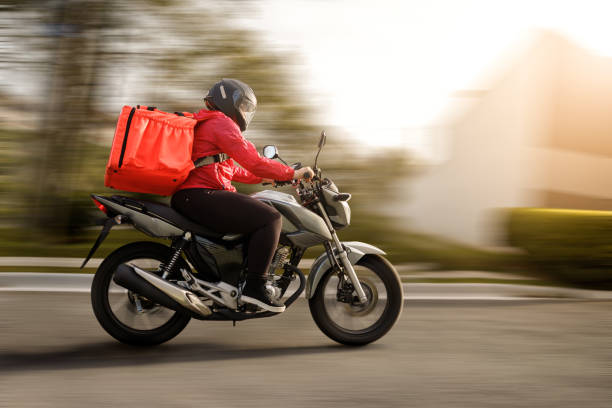 Delivery biker arriving at destination - motogirl Delivery biker arriving at destination - motogirl delivery man stock pictures, royalty-free photos & images