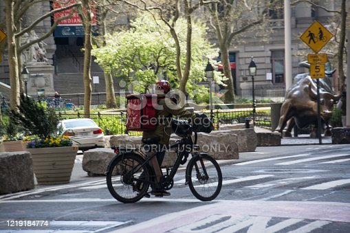 New York City, United States - April 15th, 2020: A delivery biker in downtown manhattan during Covid-19 Pandemic